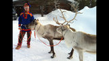 FILE - In this March 2013 file photo, A Sami handler in traditional clothing holds two of his reindeer herd in Saariselka, Finnish Lapland. The Finnish Defense Forces says 12 military conscripts ended up in the hospital after an armored personnel carrier tried to avert a reindeer and was hit by a second vehicle. The defense forces said five men remained under observation on Wednesday while the rest have returned to training after Tuesday's crash in Finland's Lapland region. (AP Photo/ David McDougall, File)