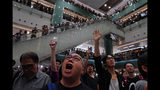 """Local residents sing a theme song written by protesters """"Glory be to thee"""" at a shopping mall in Hong Kong Wednesday, Sept. 11, 2019. Hundreds of Hong Kong citizens gathered at several malls late Wednesday, chanting slogans and belting out a new protest song. The song, """"glory to Hong Kong"""", was penned online and has been embraced by protesters as their anthem song. The peaceful mall gatherings marked a respite after violent clashes over the weekend. (AP Photo/Vincent Yu)"""