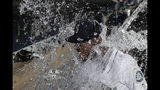 Seattle Mariners right fielder Kyle Lewis is doused with water by a teammate as he takes part in an interview following the team's baseball game against the Cincinnati Reds, Tuesday, Sept. 10, 2019, in Seattle. Lewis hit a solo home run in his major league debut as the Mariners won 4-3. (AP Photo/Ted S. Warren)