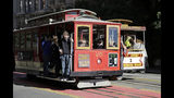 FILE - In this Nov. 3, 2015 file photo, a pair of cable cars go past each other on Powell Street atop Nob Hill in San Francisco. The city's iconic cable cars will stop running for 10 days starting Friday, Sept. 13, 2019, while they undergo repairs. The San Francisco Municipal Transportation Agency said Wednesday, Sept. 11, that instead shuttle buses will run along the three cable car routes. The agency says it needs to get the manually-operated cable cars off the street to rehabilitate the gearboxes that power the system that started in the 1890s. (AP Photo/Eric Risberg, File)