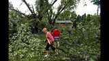 Neighbors join together to clear debris from Lindsey Waggoner's backyard after a tree fell and power lines were downed on Wednesday, Sept. 11, 2019, in Sioux Falls, S.D. Meteorologist Todd Heitkamp said Wednesday that the National Weather Service has confirmed that three EF-2 tornadoes hit the city. (Erin Bormett/The Argus Leader via AP)
