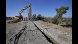 Government contractors erect a section of Pentagon-funded border wall along the Colorado River, Tuesday, Sept. 10, 2019 in Yuma, Ariz. The 30-foot high wall replaces a five-mile section of Normandy barrier and post-n-beam fencing, shown at left, along the the International border that separates Mexico and the United States. Construction began as federal officials revealed a list of Defense Department projects to be cut to pay for President Donald Trump's wall. (AP Photo/Matt York)