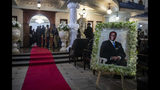 A portrait of former president Robert Mugabe stands outside the room where his body lies in state inside his official residence in the capital Harare, Zimbabwe Wednesday, Sept. 11, 2019. Zimbabwe's founding leader Robert Mugabe made his final journey back to the country Wednesday, his body flown into the capital amid the contradictions of his long, controversial rule. (AP Photo/Ben Curtis)