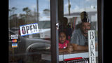 A man and girl peer out from a bakery and cafeteria in Freeport, Bahamas, Wednesday, Sept. 11, 2019. Those who survived Hurricane Dorian are facing the prospect of starting their lives over but with little idea of how or where to even begin. (AP Photo/Ramon Espinosa)