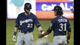 Milwaukee Brewers' Christian Yelich (22) is congratulated by first base coach Carlos Subero (31) after getting a base hit during the first inning of a baseball game against the Miami Marlins, Monday, Sept. 9, 2019, in Miami. (AP Photo/Wilfredo Lee)