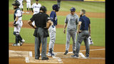 Milwaukee Brewers' Christian Yelich, second from left, is checked on by home plate umpire Kerwin Danley, manager Craig Counsell, second from right, and a trainer after an injury while batting during the first inning of the team's baseball game against the Miami Marlins, Tuesday, Sept. 10, 2019, in Miami. Yelich broke his right kneecap on a foul ball and will miss the rest of the regular season. (AP Photo/Wilfredo Lee)