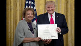 FILE - In this Sept. 9, 2019, file photo, President Donald Trump presents a Certificate of Commendation to Minnie Grant, the mother of Christopher Grant, one of five civilians celebrated for their heroism during a mass shooting in El Paso, Texas, at a ceremony in the East Room of the White House in Washington. El Paso police say surveillance video does not back up the story told by Grant. Grant has said he threw bottles to try to stop the attack, which left 22 people dead. Grant, who was shot twice, was among those recognized this week by President Trump, although his mother received the certificate because Grant had been temporarily detained by the U.S. Secret Service because of an outstanding warrant. (AP Photo/Andrew Harnik, File)