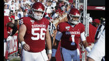 In this photo taken Sept. 7, 2019, Oklahoma offensive lineman Creed Humphrey (56) and quarterback Jalen Hurts (1), two of the team's captains, walk onto the field before an NCAA college football game against South Dakota in Norman, Okla. Oklahoma lost four starters from last year's offensive line to the NFL draft, but this year's unit has fueled an attack that leads the nation in total offense. (AP Photo/Sue Ogrocki)