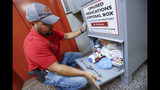 In this Sept. 11, 2019, photo, narcotics detective Paul Laurella retrieves unused medications from the police department's disposal box in Barberton, Ohio. The tentative settlement involving the opioid crisis and the maker of OxyContin, Purdue Pharma, could mean that thousands of local governments will one day be paid back for some of the costs of responding to the epidemic. (AP Photo/Keith Srakocic)