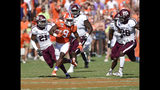 Clemson's Travis Etienne (9) rushes while defended by Texas A&M's Charles Oliver (21) and Demani Richardson (26) during the first half of an NCAA college football game Saturday, Sept. 7, 2019, in Clemson, S.C. (AP Photo/Richard Shiro)