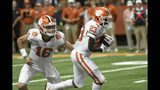 Clemson's Lyn-J Dixon takes a handoff from quarterback Trevor Lawrence during the first half of the team's NCAA college football game against Syracuse on Saturday, Sept. 14, 2019, in Syracuse, N.Y. (AP Photo/Steve Jacobs)