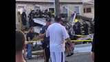 In this photo provided by James Macheda, one of the first responders talks to an onlooker as others carry an injured person, while some others work the scene of a building structure damage, in the background, in Wildwood, N.J., Saturday, Sept. 14, 2019. Multiple levels of decking attached to a building collapsed Saturday evening at the Jersey Shore, trapping people and injuring several, including children, officials and witnesses said. (James Macheda via AP)
