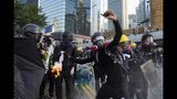 An anti-government protester throws a Molotov cocktail during a demonstration near Central Government Complex in Hong Kong, Sunday, Sept. 15, 2019. Police fired a water cannon and tear gas at protesters who lobbed Molotov cocktails outside the Hong Kong government office complex Sunday, as violence flared anew after thousands of pro-democracy supporters marched through downtown in defiance of a police ban. (AP Photo/Vincent Yu)