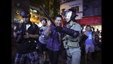 A Pro-China supporter, center, is escorted by police after confronting journalists in north point, Hong Kong, Sunday, Sept. 15, 2019. Police fired a water cannon and tear gas at protesters who lobbed Molotov cocktails outside the Hong Kong government office complex Sunday, as violence flared anew after thousands of pro-democracy supporters marched through downtown in defiance of a police ban. (AP Photo/Vincent Yu)