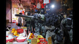 Police arrive after pro-China supporters confront with journalists in north point, at a local market of Hong Kong, Sunday, Sept. 15, 2019. Police fired a water cannon and tear gas at protesters who lobbed Molotov cocktails outside the Hong Kong government office complex Sunday, as violence flared anew after thousands of pro-democracy supporters marched through downtown in defiance of a police ban. (AP Photo/Kin Cheung)