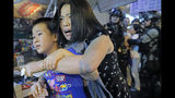 Mother and son leave as police arrive after pro-China supporters confronted with journalists in north point, at a local market of Hong Kong, Sunday, Sept. 15, 2019. Police fired a water cannon and tear gas at protesters who lobbed Molotov cocktails outside the Hong Kong government office complex Sunday, as violence flared anew after thousands of pro-democracy supporters marched through downtown in defiance of a police ban. (AP Photo/Kin Cheung)