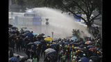 Anti-government protesters are sprayed by a water cannon during a demonstration near Central Government Complex in Hong Kong, Sunday, Sept. 15, 2019. Police fired a water cannon and tear gas at protesters who lobbed Molotov cocktails outside the Hong Kong government office complex Sunday, as violence flared anew after thousands of pro-democracy supporters marched through downtown in defiance of a police ban. (AP Photo/Kin Cheung)