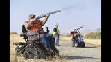 "FILE - In this Nov. 16, 2018, file photo, Duane Townsend, left, shoots a pheasant at Special Friday Pheasant Hunts, sponsored by Southern Tulare County Sportsman's Association, at Lake Success Recreation Area in Porterville, Calif. A Utah man who has been in a wheelchair for more than three decades has created a pheasant hunt for people like him who need help getting into the outdoors. The Daily Herald in Provo reports that Clint Robinson broke his neck after being thrown off a horse at a rodeo 32 years ago. The event called ""Wheelchairs in the Wild"" pairs people that have physical disabilities with hunters who help them with whatever they need. Many go in off-road vehicles. (Chieko Hara/The Porterville Recorder via AP, File)"