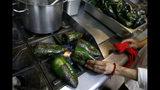 En esta imagen del 13 de septiembre de 2019, una cocinera asa chiles poblanos en el fuego antes de retirarles la piel, mientras el personal de cocina prepara chiles en nogada en el restaurante Testal, en el centro de Ciudad de México. Testal ha dedicado casi una cocina entera a preparar el emblemático platillo y vende unos 150 al día. Este año intentan vender más del doble de los 3.000 que sirvieron el año pasado en la corta temporada. (AP Foto/Rebecca Blackwell)