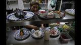 En esta imagen del 13 de septiembre de 2019, una cocinera prepara chiles en nogada para los comensales en el restaurante Testal, en el centro de Ciudad de México. Testal ha dedicado casi una cocina entera a producir el emblemático platillo y vende unos 150 al día. Este año, esperan vender más del doble de los 3.000 que sirvieron el año pasado en la breve temporada. (AP Foto/Rebecca Blackwell)
