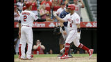 Los Angeles Angels designated hitter Albert Pujols, right, gets congratulations from Andrelton Simmons, after Pujols hit a three-run home run against the Tampa Bay Rays during the fifth inning of a baseball game in Anaheim, Calif., Sunday, Sept. 15, 2019. (AP Photo/Alex Gallardo)
