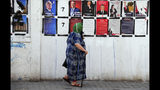 A woman pauses as she walks past candidates' posters and designated numbers a day before the start of presidential election in Tunis, Tunisia, Saturday, Sept. 14, 2019. (AP Photo/Hassene Dridi)