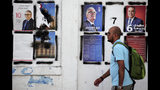 A man walks past candidates' posters and designated numbers a day before the start of presidential election in Tunis, Tunisia, Saturday, Sept. 14, 2019. (AP Photo/Hassene Dridi)