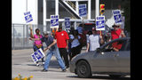 Gary Allison, left, waves while standing with other union members picketing outside the General Motors Plant in Arlington, Texas, Monday, Sept. 16, 2019. More than 49,000 members of the United Auto Workers walked off General Motors factory floors or set up picket lines as contract talks with the company deteriorated into a strike. (AP Photo/LM Otero)