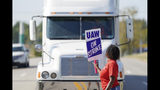 A striking plant worker blocks the passage of a truck outside the General Motor assembly plant in Bowling Green, Ky, Monday, Sept. 16, 2019. More than 49,000 members of the United Auto Workers walked off General Motors factory floors or set up picket lines early Monday as contract talks with the company deteriorated into a strike. (AP Photo/Bryan Woolston)