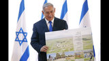 Israeli Prime Minister Benjamin Netanyahu holds up a placard given to him as a gift from Israeli residents of the area, at the start of a weekly cabinet meeting being held in a makeshift tent in the Jordan Valley, in the Israeli-occupied West Bank, Sunday, Sept. 15, 2019. Netanyahu convened his final pre-election cabinet meeting in a part of the West Bank that he's vowed to annex if re-elected. National elections are on Tuesday. (Amir Cohen/Pool via AP)
