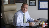 In this Friday, Sept. 13, 2019, photo, Mayor Craig Johnson poses for a photograph in his office in Elk Grove Village, Ill. While the nation's attorneys general debate a legal settlement with Purdue Pharma, the opioid epidemic associated with the company's blockbuster painkiller OxyContin rages on. Johnson created a program in which addicted people can ask police officers and other municipal workers for help without fear of arrest, even if they have illegal drugs or paraphernalia. (AP Photo/Teresa Crawfor)