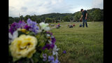 FILE - In this July 17, 2019 file photo, Eddie Davis steps up to the gravestone of his son Jeremy, who died from the abuse of opioids in Coalton, Ohio. While the nation's attorneys general debate a legal settlement with Purdue Pharma, the opioid epidemic associated with the company's blockbuster painkiller OxyContin rages on. The drugs still kill tens of thousands of people each year with no end in sight. (AP Photo/John Minchillo, File)