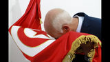 Kais Saied, a constitutional law professor without a party, kisses the national flag after hearing the unofficial results of the presidential elections, Sunday, Sept.15, 2019. A jailed media magnate and an independent outsider appeared likely to face off in Tunisia's presidential runoff, after a roller coaster first-round race in the country that unleashed the Arab Spring pro-democracy uprisings. (Photo/STR)