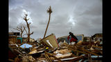 Vladimir Safford an immigrant from Haiti walks through the rubble next to his home in the aftermath of Hurricane Dorian in Abaco, Bahamas, Monday, Sept. 16, 2019. Dorian hit the northern Bahamas on Sept. 1, with sustained winds of 185 mph (295 kph), unleashing flooding that reached up to 25 feet (8 meters) in some areas. (AP Photo/Ramon Espinosa)