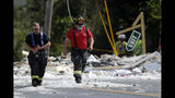 Firefighters walk through the scene of an explosion Monday, Sept. 16, 209, in Farmington, Maine. Officials say a town's fire chief is among the injured in a propane explosion that killed a firefighter. State public safety spokesman Steve McCausland said after Monday morning's explosion at a nonprofit center in Farmington that multiple people remain hospitalized. (AP Photo/Robert F. Bukaty)