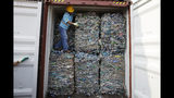 A worker stands inside a container full of plastic waste at Tanjung Priok port in Jakarta, Indonesia Wednesday, Sept. 18, 2019. Indonesia is sending hundreds of containers of waste back to Western nations after finding they were contaminated with used plastic and hazardous materials. (AP Photo/Achmad Ibrahim)