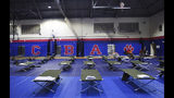 Cots fill the gym at Cedarbridge Academy which will be used as a shelter during the passing of Hurricane Humberto in Devonshire, Bermuda, Wednesday, Sept. 18, 2019. Bermuda's government called up troops and urged people on the British Atlantic island to make final preparations for an expected close brush Wednesday with Hurricane Humberto, a powerful Category 3 storm. Authorities ordered early closings of schools, transportation and government offices. (AP Photo/Akil J. Simmons)