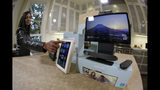 In this photo taken Tuesday, Sept. 17, 2019, new Facebook Portal products are displayed during an event in San Francisco. At left being demonstrated is the Portal Mini and at right is Portal TV. Facebook is slashing the price and the size of the Portal, its screen and camera-equipped gadget for making video calls with friends and family as it attempts to get the device into more homes. A smaller version will now cost $129 and have an 8 inch display. A larger version will cost $179 and have a 10 inch display. (AP Photo/Eric Risberg)