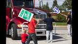 Retired GM union member Roxanne Williams, 63, stood-up to a semi-truck attempting to enter the GM Davison Road Processing Center. United Automobile Workers remain on strike against GM on Tuesday, Sept. 17, 2019 in Burton, Mich. Williams has worked for GM for 20 years. (Sara Faraj/The Flint Journal via AP)