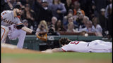 Boston Red Sox's Sam Travis, right, dives to third base for a triple as San Francisco Giants' Evan Longoria, left, tries to field the ball during the sixth inning of a baseball game at Fenway Park in Boston, Tuesday, Sept. 17, 2019. Travis left the game after the play. (AP Photo/Charles Krupa)