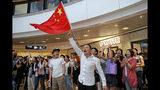 Partidarios del gobierno de Beijing ondean una bandera nacional china en un centro comercial en Hong Kong, el miércoles 18 de septiembre de 2019. (AP Foto/Kin Cheung)