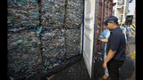 Indonesian customs officers lock containers full of plastic at Tanjung Priok port in Jakarta, Indonesia Wednesday, Sept. 18, 2019. Indonesia is sending hundreds of containers of waste back to Western nations after finding they were contaminated with used plastic and hazardous materials. (AP Photo/Achmad Ibrahim)