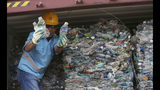 A worker shows plastic waste at Tanjung Priok port in Jakarta, Indonesia Wednesday, Sept. 18, 2019. Indonesia is sending hundreds of containers of waste back to Western nations after finding they were contaminated with used plastic and hazardous materials. (AP Photo/Achmad Ibrahim)