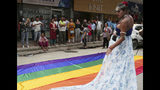 In this Aug. 16, 2019, photo, a participant stands beside a rainbow flag before a gay pride parade in Kathmandu, Nepal. Nepal seized the lead in equal rights for sexual minorities in South Asia four years ago with a new constitution that forbids all discrimination based on sexual orientation. But activists say progress in equal rights has stalled since the constitution was adopted. (AP Photo/Niranjan Shrestha)