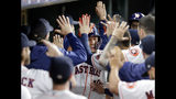 Houston Astros' Yuli Gurriel, center, collects high fives in the dugout after his two-run home run during the fifth inning of a baseball game against the Texas Rangers Wednesday, Sept. 18, 2019, in Houston. (AP Photo/Michael Wyke)