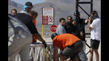 """Workers erect a stage near a replica Area 51 gate sign at the Alien Research Center, Wednesday, Sept. 18, 2019, in Hiko, Nev. Visitors descending on the remote Nevada desert for """"Storm Area 51"""" are from Earth, not outer space. No one knows what to expect, but the two tiny towns of Rachel and Hiko near the once-secret military research site are preparing for an influx of people over the next few days. (AP Photo/John Locher)"""