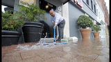 Paco Vargas pushes floodwaters from Tropical Depression Imelda away from his business Wednesday, Sept. 18, 2019, in Galveston, Texas. (AP Photo/David J. Phillip)