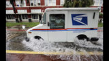 A postal truck drives through floodwaters from Tropical Depression Imelda, Wednesday, Sept. 18, 2019, in Galveston, Texas. (AP Photo/David J. Phillip)
