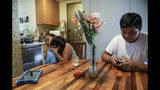 En esta foto del miércoles 21 de agosto de 2019, la inmigrante guatemalteca Rosayra Pablo Cruz, a la izquierda, consuela a su hijo menor Fernando, de 6 años, con un abrazo, mientras que Yordy, de 17 años, usa su teléfono celular en la cocina de la planta baja de su hogar de acogida en Nueva York. (AP Foto / Bebeto Matthews)