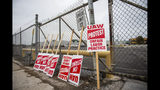 United Auto Workers protest signs lean against the fence at GM Powertrain in Bay City, Mich., on Monday, Sept. 16, 2019. (Kaytie Boomer/The Bay City Times via AP)